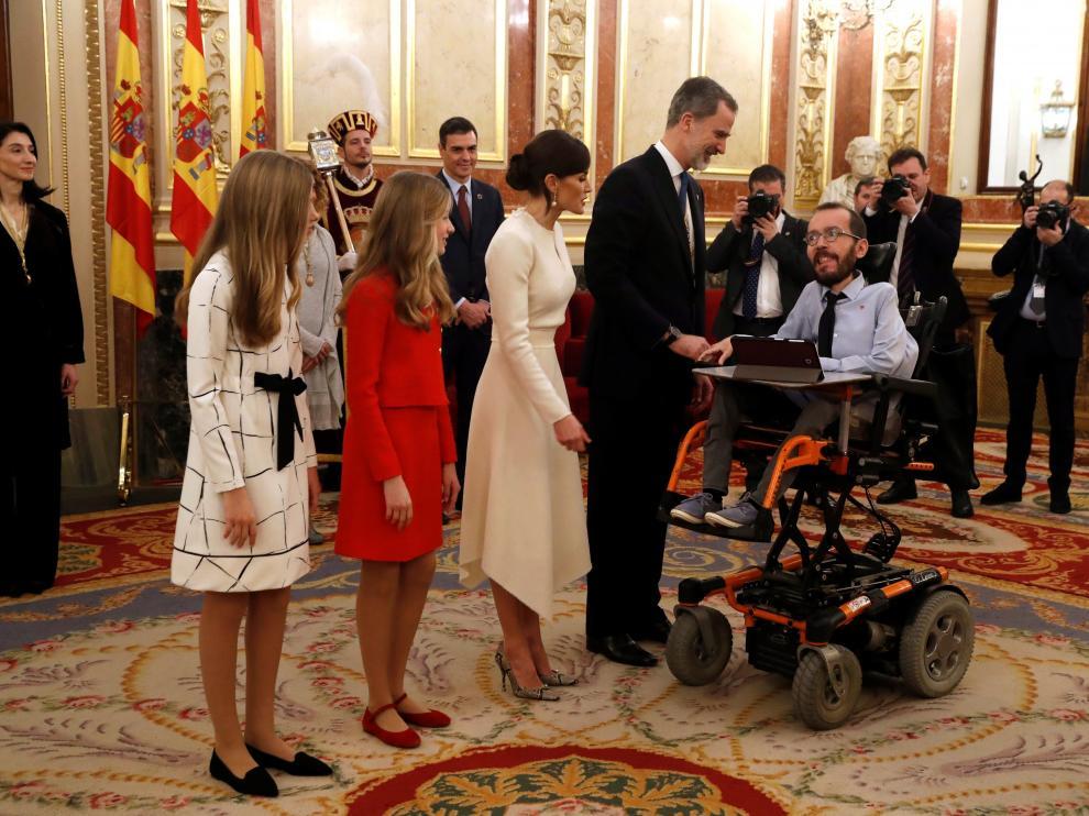 Los Reyes y sus hijas saludan al portavoz de Podemos, Pablo Echenique, en la apertura de la legislatura en el Congreso de los Diputados.