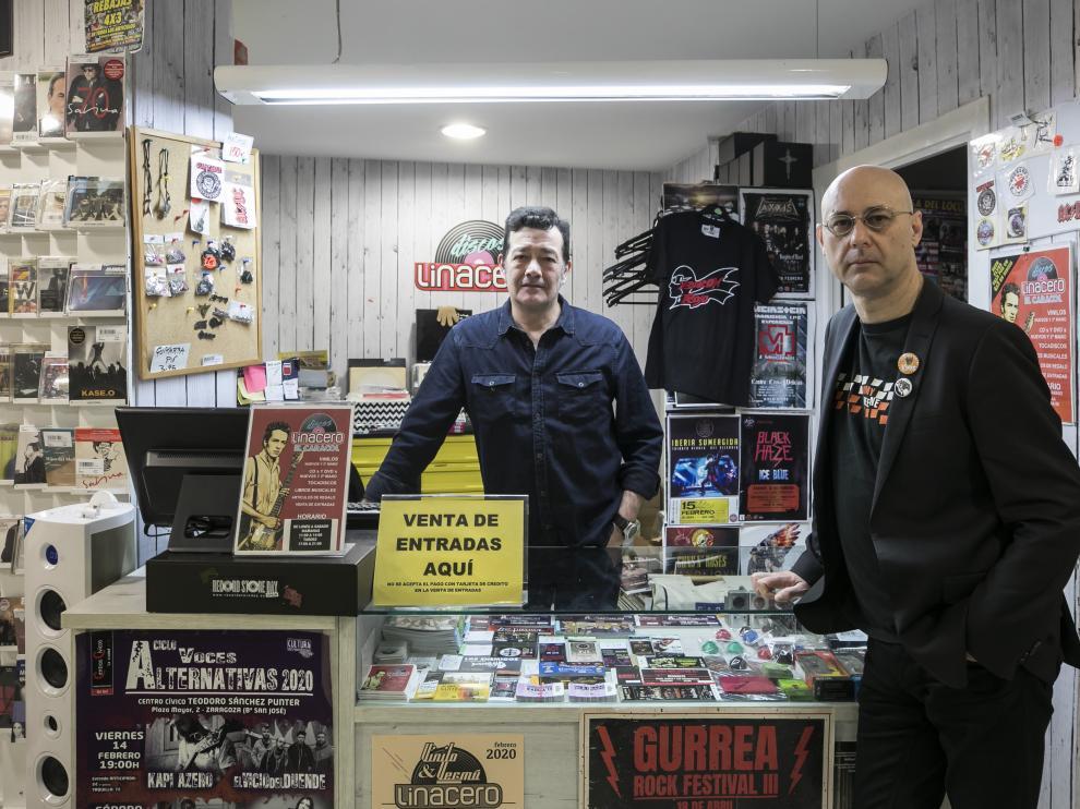 Luis Linacero (izquierda) y Chema Fernández, en Discos Linacero, apoyados en un expositor lleno de tacos de entradas.