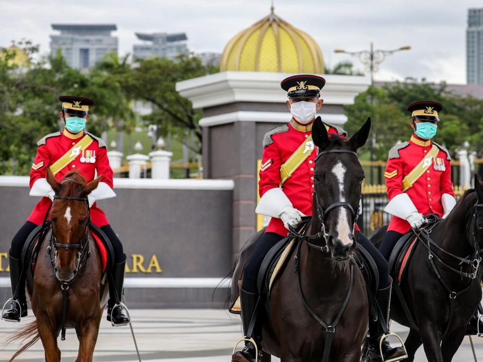 Los guardias reales de Malasia usan máscaras protectoras mientras hacen guardia afuera del Palacio Nacional, en Kuala Lumpur