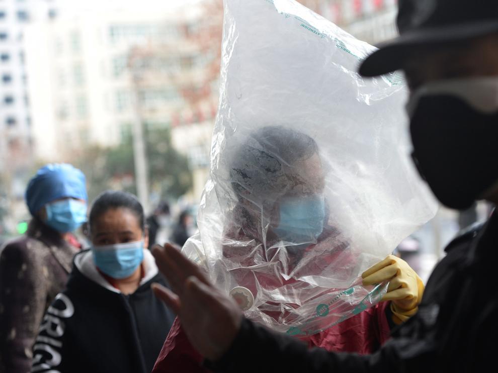 Un ciudadano chino protegido con una bolsa de plástico sobre la cabeza
