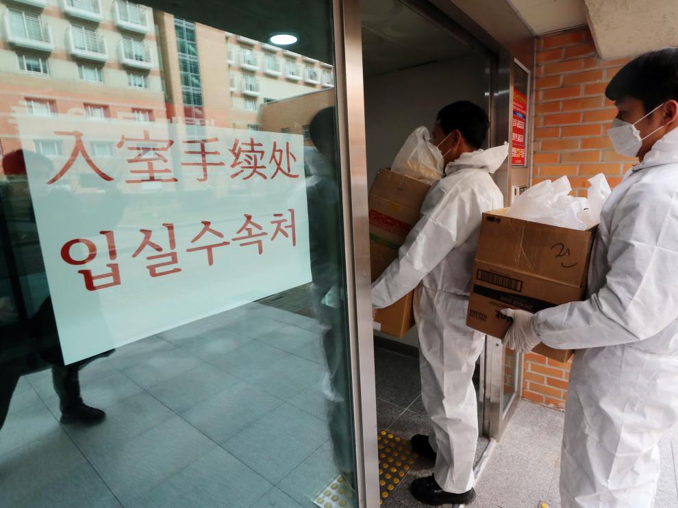 Empleados de la Universidad Nacional de Chunnam en Gwangju (Corea del Sur) se protegen para entregar comida a un grupo de estudiantes chinos que fueron aislados por el coronavirus