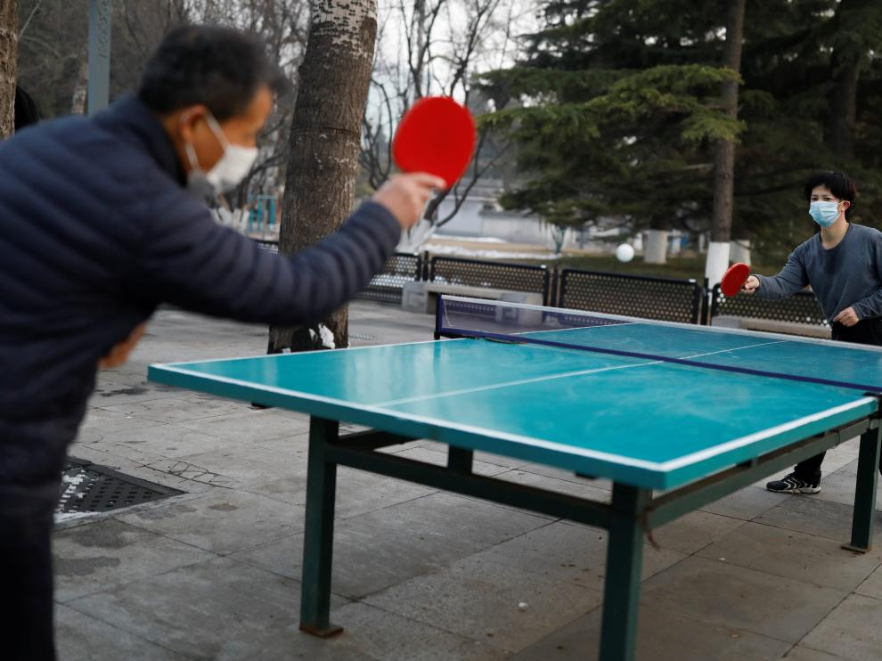 Dos personas con mascarilla juegan al tenis de mesa en un parque de Pekín