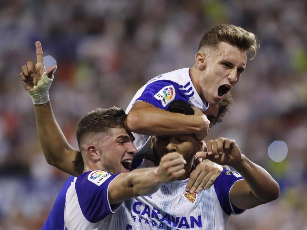 Álex Blanco y Guti abrazan a Luis Suárez, autor del único gol (de penalti) en la victoria del encuentro de ida entre el Real Zaragoza y el Elche