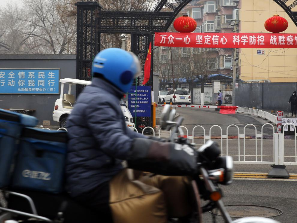 Beijing (China), 13/02/2020.- A food delivery man riding bicycle pass a banner reading 'Unite as one, firm confidence, scientific prevention and control, and defeat the epidemic' in Beijing, China, 13 February 2020. The disease caused by the novel coronavirus (SARS-CoV-2) has been officially named Covid-19 by the World Health Organization (WHO). The outbreak, which originated in the Chinese city of Wuhan, has so far killed at least 1,369 people with over 60,000 infected worldwide, mostly in China. EFE/EPA/WU HONG Propaganda banners about coronavirus in Beijing