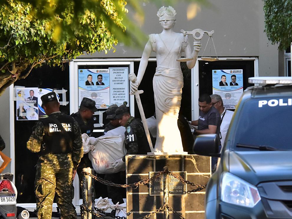 Un grupo de policías lleva el cuerpo sin vida de uno de los agentes asesinados en el juzgado de la ciudad de El Progreso
