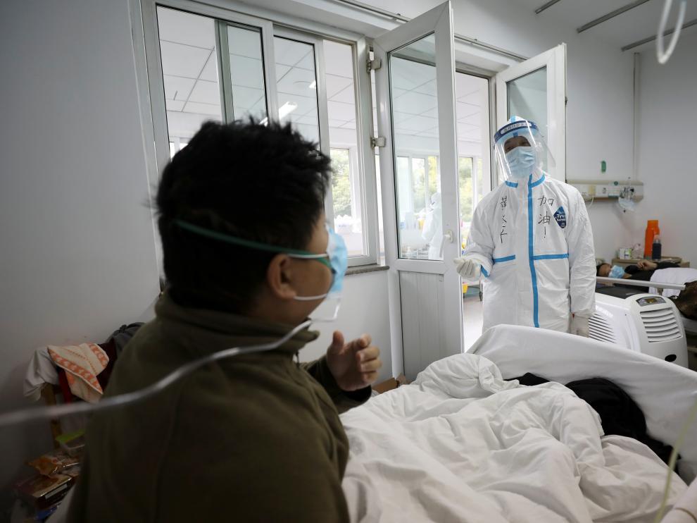 Un profesional sanitario con el traje de seguridad interactúa con un paciente en una habitación de aislamiento de un hospital en Wuhan.