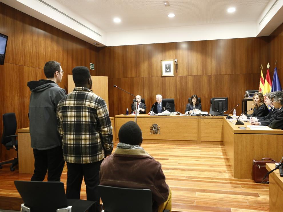 Los dos acusados, uno sentado y el otro, con la camisa a cuadros, de pie junto al intérprete de ghanés.
