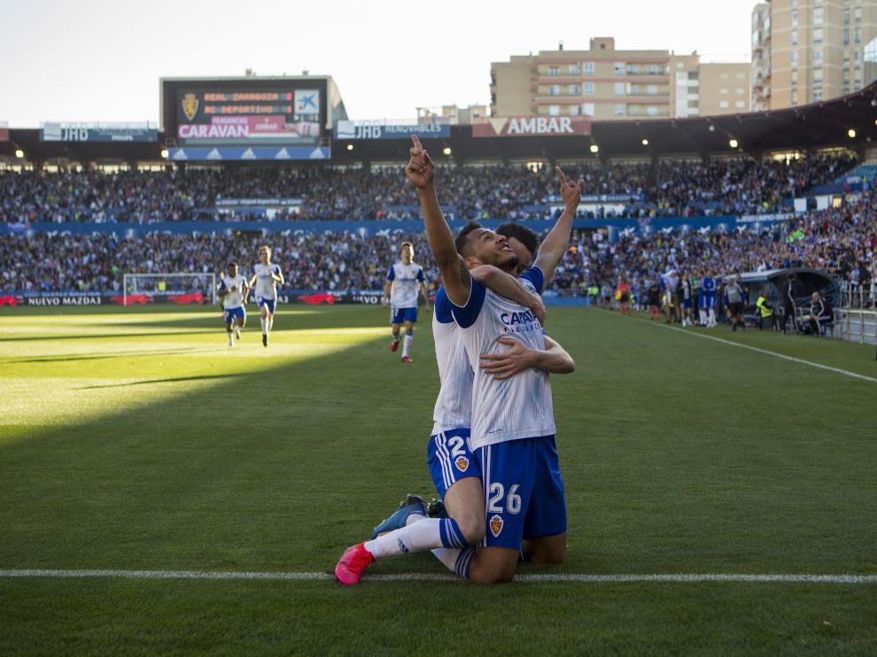 Luis Suárez, de rodillas, mira al cielo mientras es abrazado por Burgui.