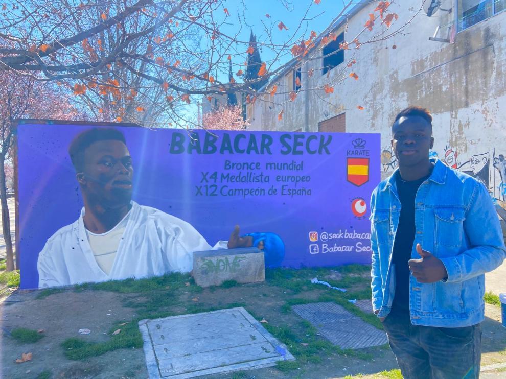 El karateca Babacar ante el grafiti que se muestra en el andador Antonio Leyva en el barrio Oliver