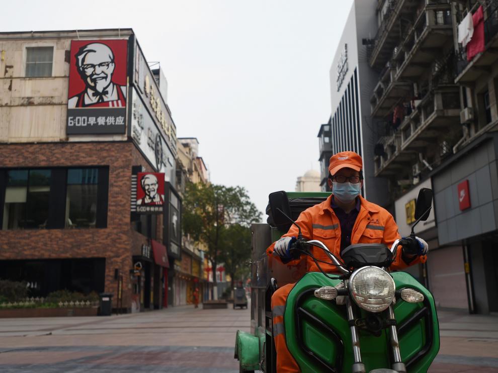 Un trabajador sanitario en su moto este martes por una calle de Wuhan, zona 0 del coronavirus.