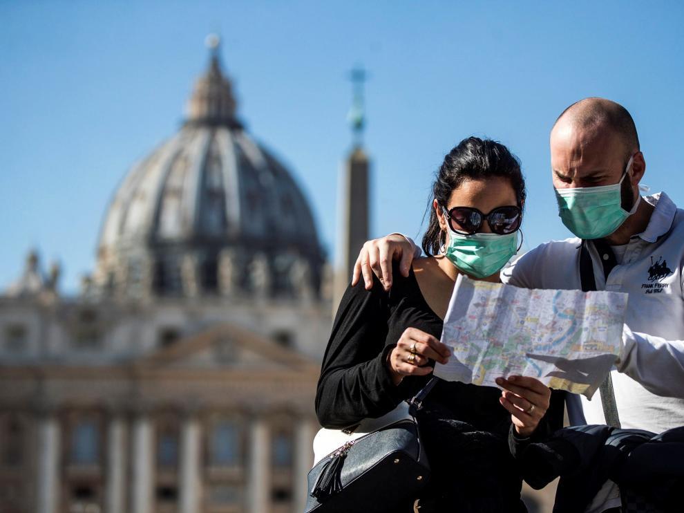 Una pareja de turistas con máscaras faciales visita la plaza de San Pedro en el Vaticano.