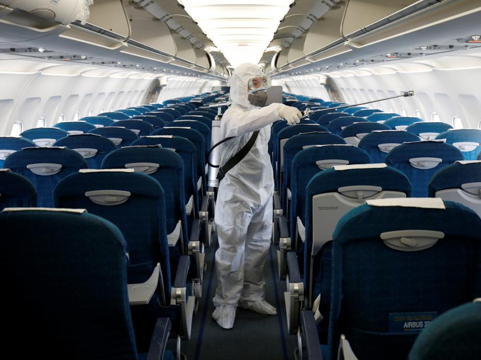 FILE PHOTO: A health worker sprays disinfectant inside a Vietnam Airlines airplane to protect against the recent coronavirus outbreak, at Noi Bai airport in Hanoi, Vietnam