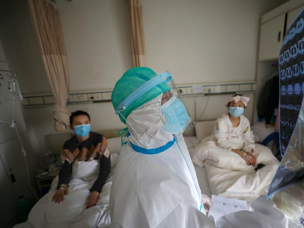 Medical worker in protective suit inspects a CT scan image at a ward of Wuhan Red Cross Hospital in Wuhan