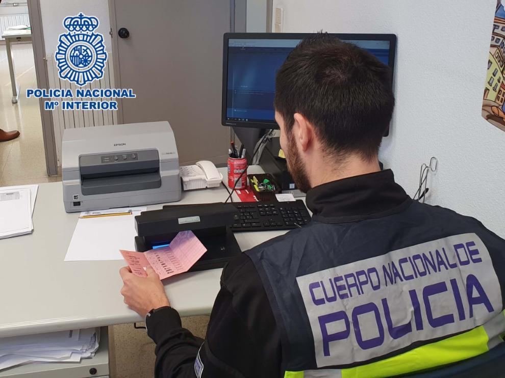 Un agente de la Policía Nacional comprueba la autenticidad del carnet de conducir del detenido.