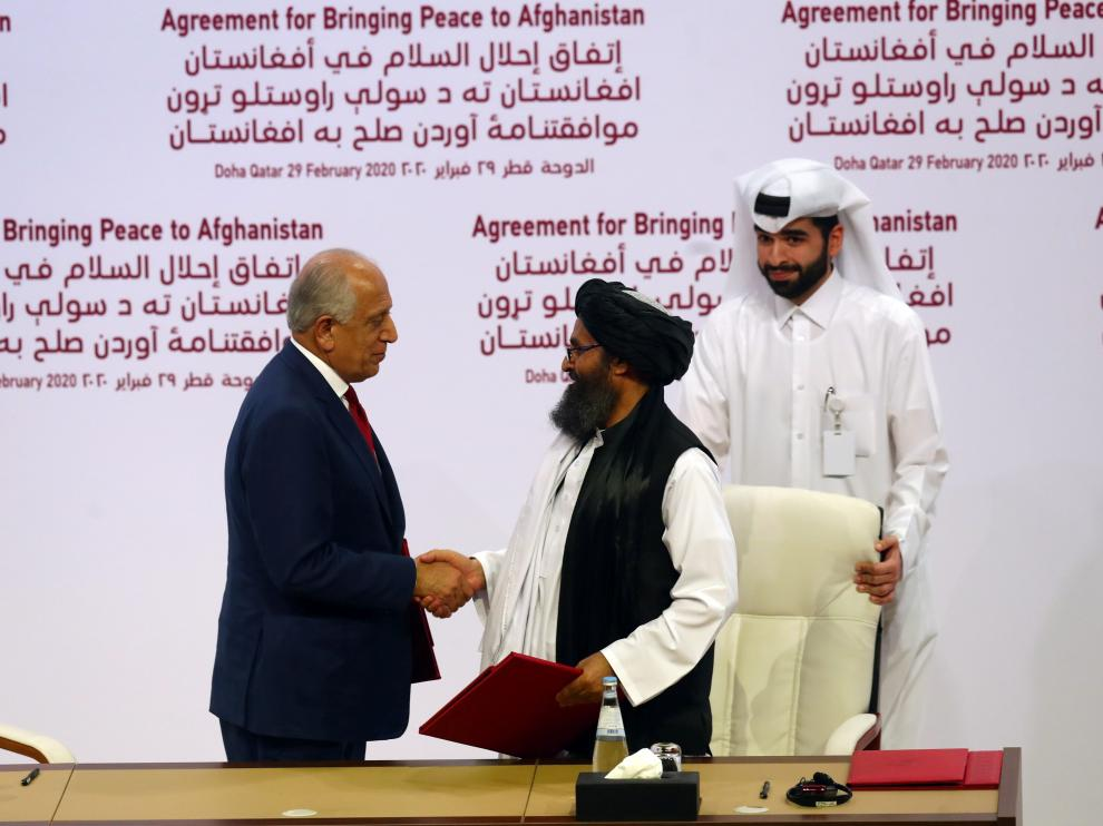 El mulá Abdul Ghani Baradar y Zalmay Khalilzad se estrechan la mano tras la firma del acuerdo.