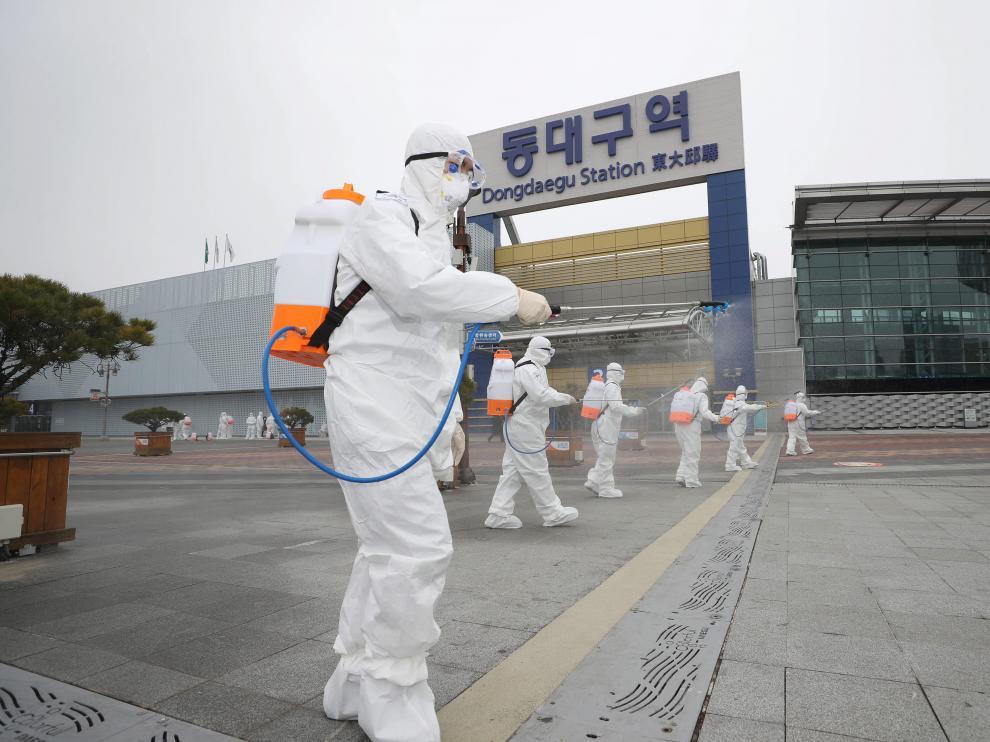 Operarios desinfectan una calle de un ciudad de Corea del Sur por el coronavirus.