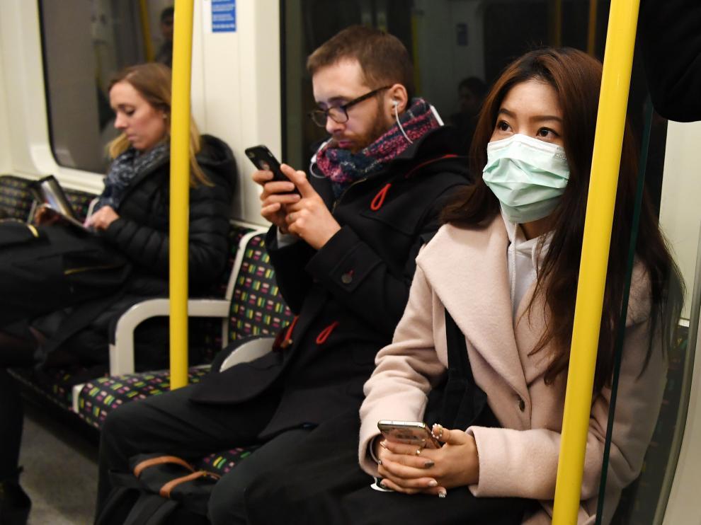 Una mujer con máscara en el metro de Lon