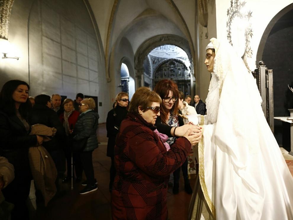 Una afiliada de la ONCE palpa a la Vuirgenla Virgen Blanca de la cofradía de El Silencio