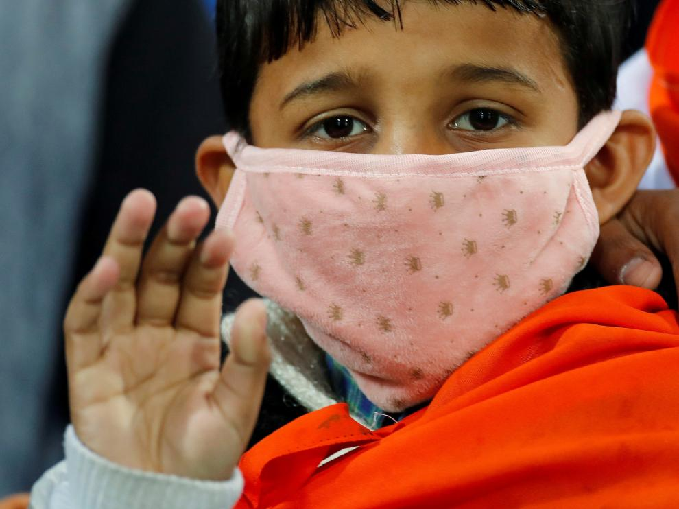 A boy wears a mask as he waits for the start of the first One-day International cricket match between India and South Africa, amid coronavirus fears, in Dharamsala