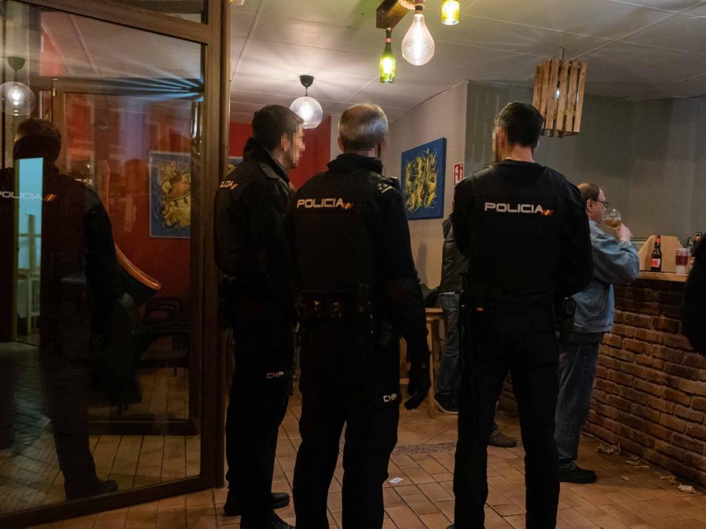 Un cliente del bar Toca Jamón apura la cerveza mientras la Policía Local clausura el local por la crisis del coronavirus.