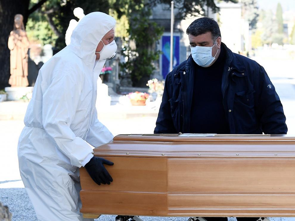 Dos personas con protección trasladan a una persona fallecida por coronavirus en Bérgamo.