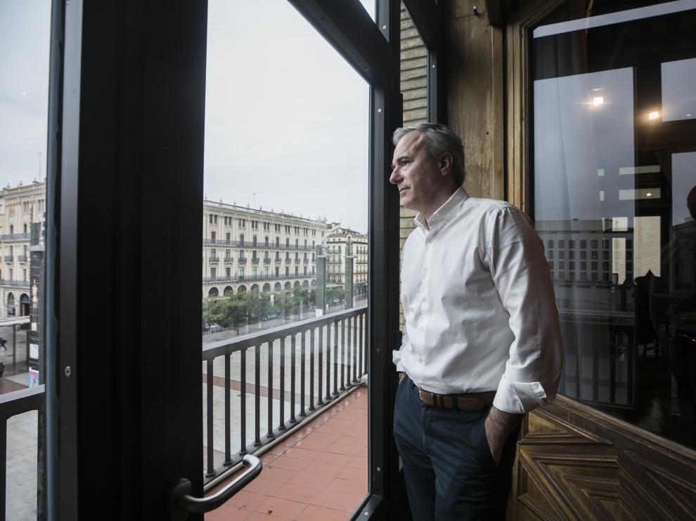 El alcalde de Zaragoza, Jorge Azcón, observa la plaza del Pilar desierta desde su despacho del Ayuntamiento.