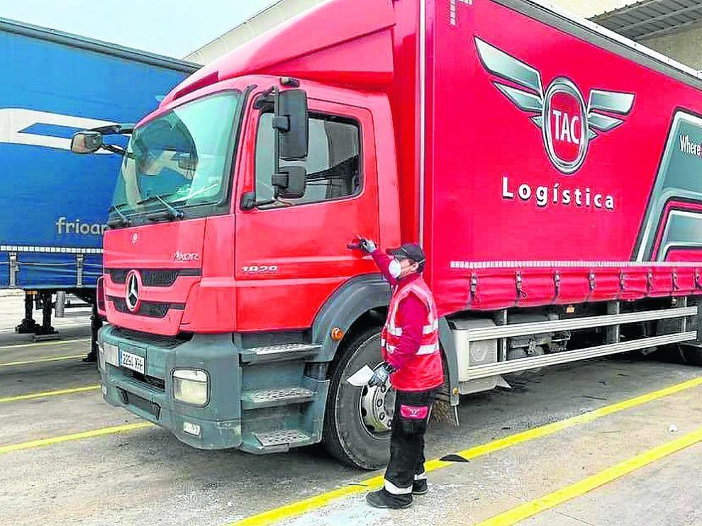 Un trabajador de la empresa zaragozana TAC Logística, junto a un camión de la firma.