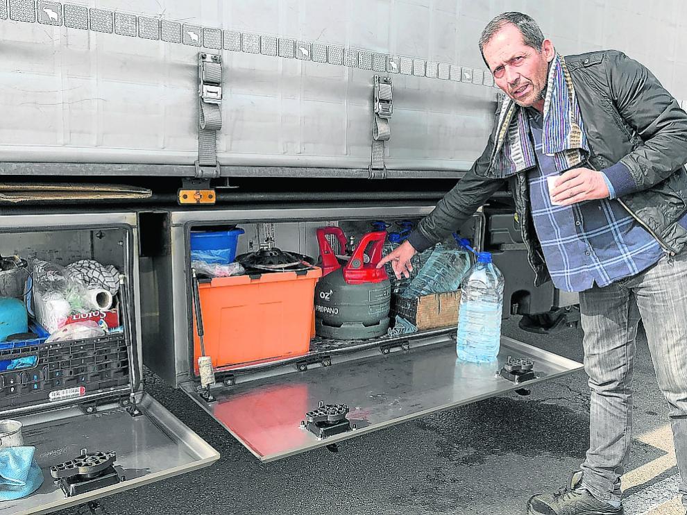 El camionero portugués Víctor Silva muestra su cocina de gas mientras toma un café