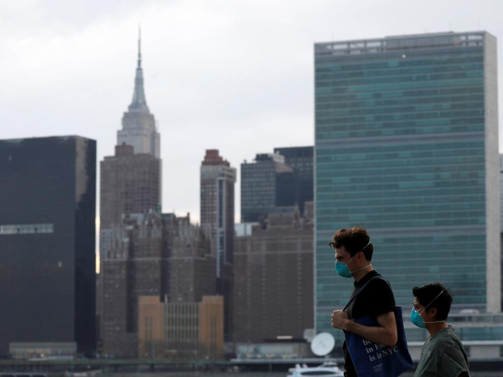 People in protective masks walk in front of the Manhattan skyline along the waterfront of Long Island City as the coronavirus disease (COVID-19) outbreak continues in the Queens borough of New York City