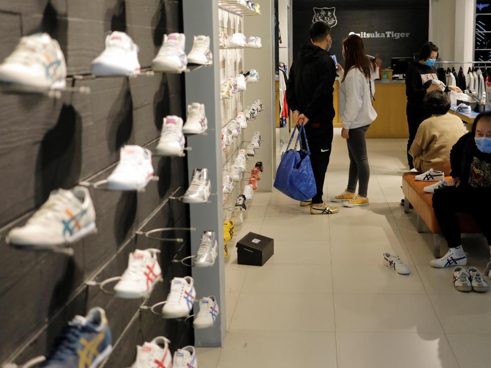 Personas con máscaras faciales compran este viernes en una zapatería de un centro comercial en Pekín.