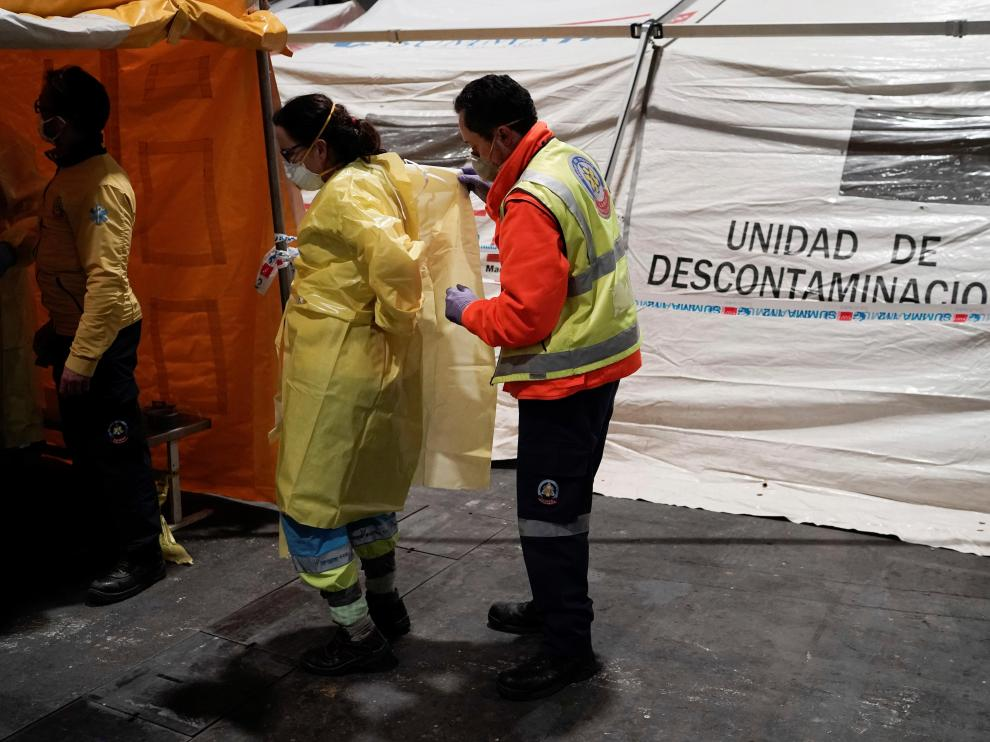 GRAF246. MADRID, 22/03/2020.- Personal sanitario accede por una zona protegida mientras comienzan a llegar los pacientes con coronavirus anoche a uno de los pabellones del recinto ferial Ifema habilitados para albergar 1.396 camas, en Madrid. EFE/ Comunidad De Madrid Llegada de pacientes al Ifema