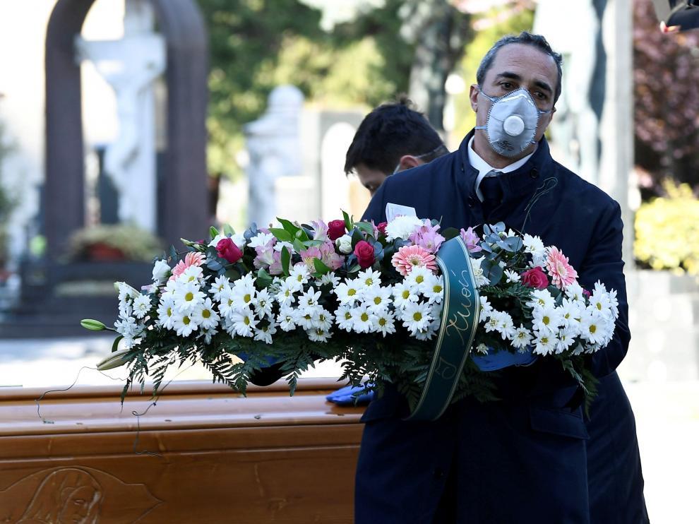 Un trabajador de una funeraria transporta una corona de flores en un cementerio de Bérgamo, en Italia.