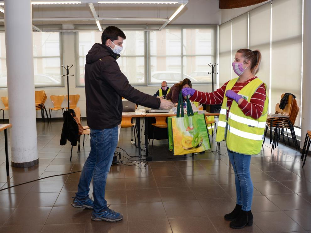 Un voluntario del programa 'Aislados pero no solos' recibe una comida preparada en Santa Emerenciana para llevarla a un anciano.