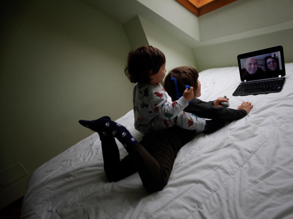 Unos chavales hablan con sus abuelos por videoconferencia durante el aislamiento.