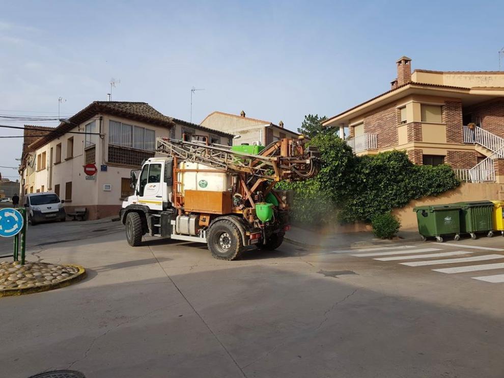 Un agricultor utiliza su maquinaria para desinfectar las calles en un municipio aragonés.