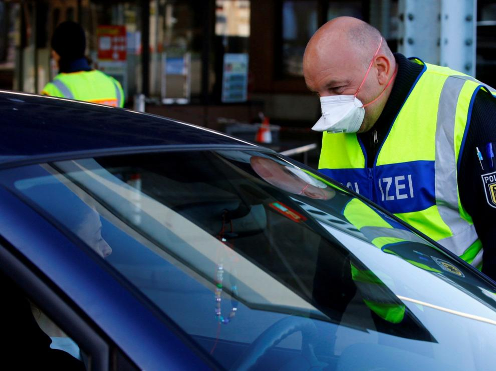FILE PHOTO: A German police officer wearing a protective face mask approaches car driver at the German-Swiss border after Germany announced border controls, March 16, 2020. REUTERS/Arnd Wiegmann/File Photo [[[REUTERS VOCENTO]]]
