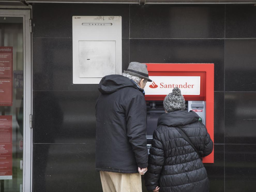 Dos clientes en un cajero de una oficina bancaria en Zaragoza.