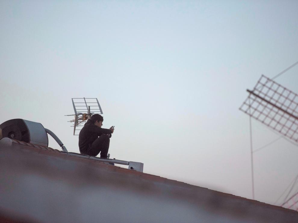 Un joven utiliza su teléfono en un tejado en tiempos de confinamiento.