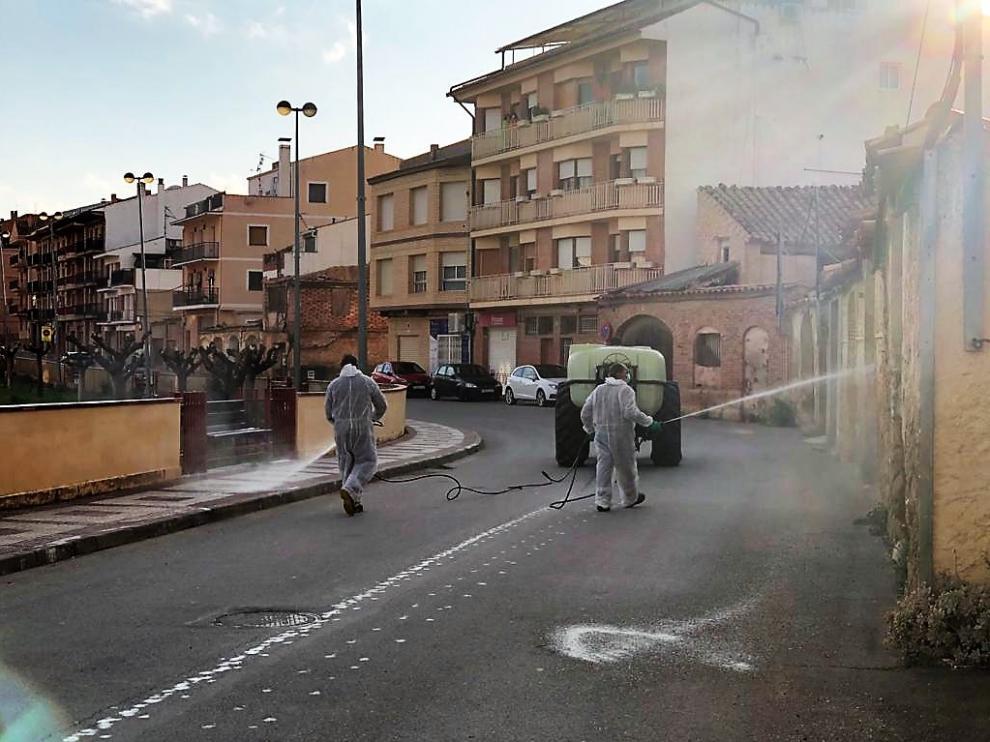 Dos operarios fumigan las calles de Alcorisa con un producto desinfectante.