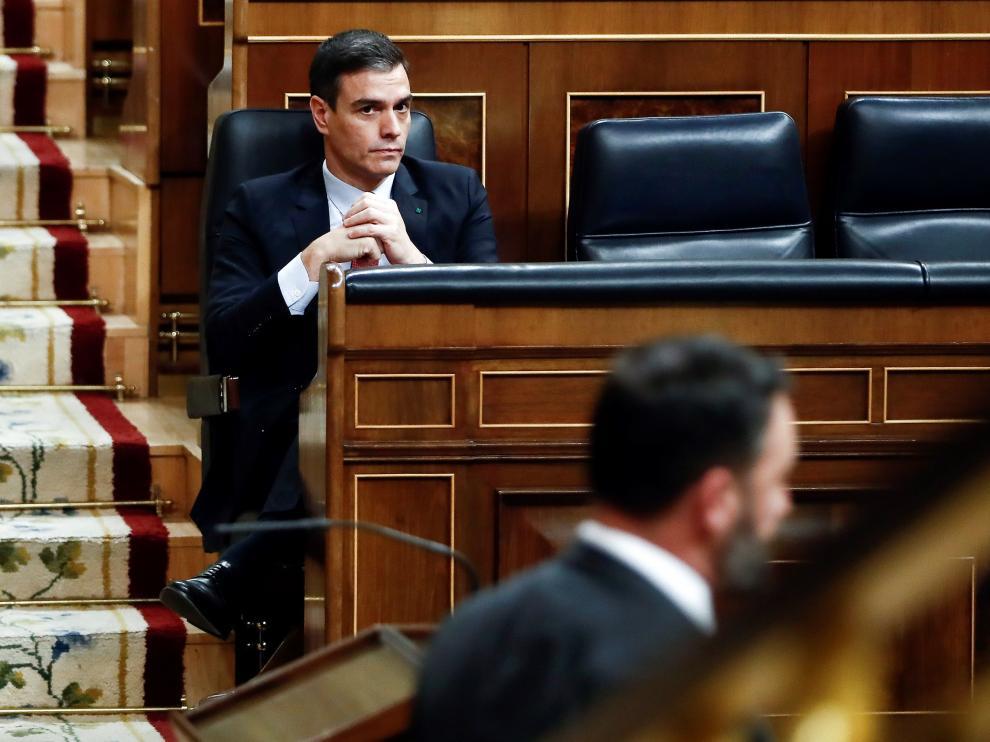 Pedro Sánchez escuchando una intervención de Santiago Abascal