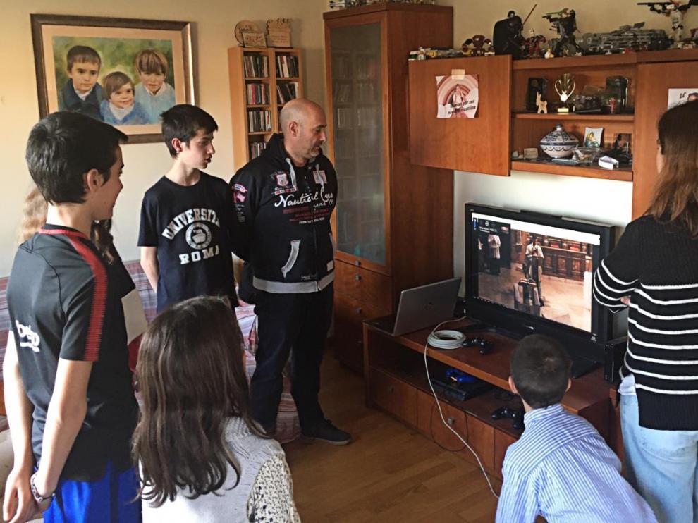 Una familia escucha la misa emitida desde Torreciudad.
