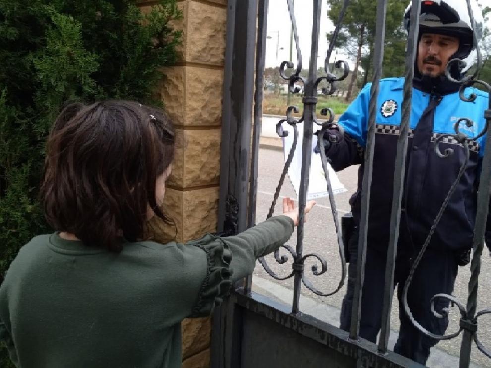 Vicente Sierra, Policía Local de Escatrón, entregando una bolsa de deberes.
