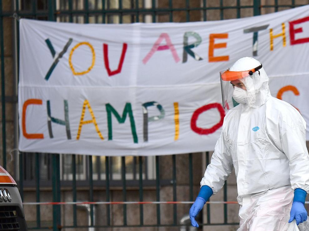 Un sanitario pasa ante una pancarta de ánimo ante un hospital en Génova.