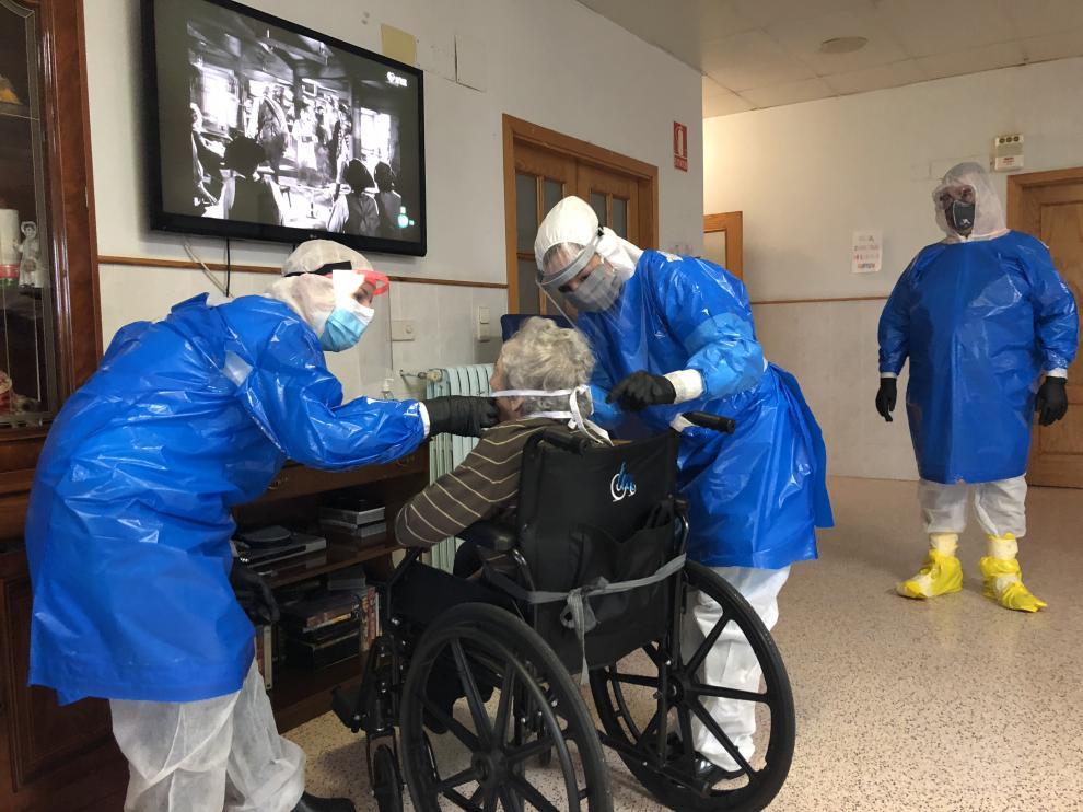 Dos voluntarias atienden a una mujer residente en la Residencia de ancianos de Épila