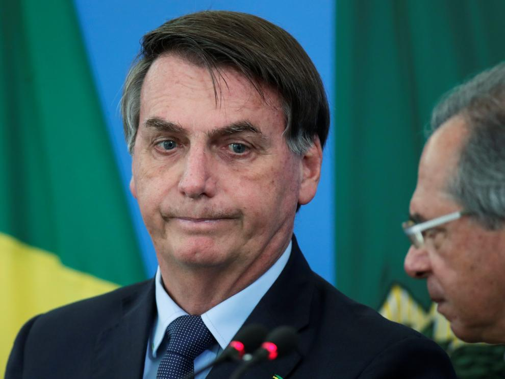 Brazil's President Jair Bolsonaro reacts near Brazil's Economy Minister Paulo Guedes during a media statement announcing economic measures, amid coronavirus disease (COVID-19) outbreak, in Brasilia