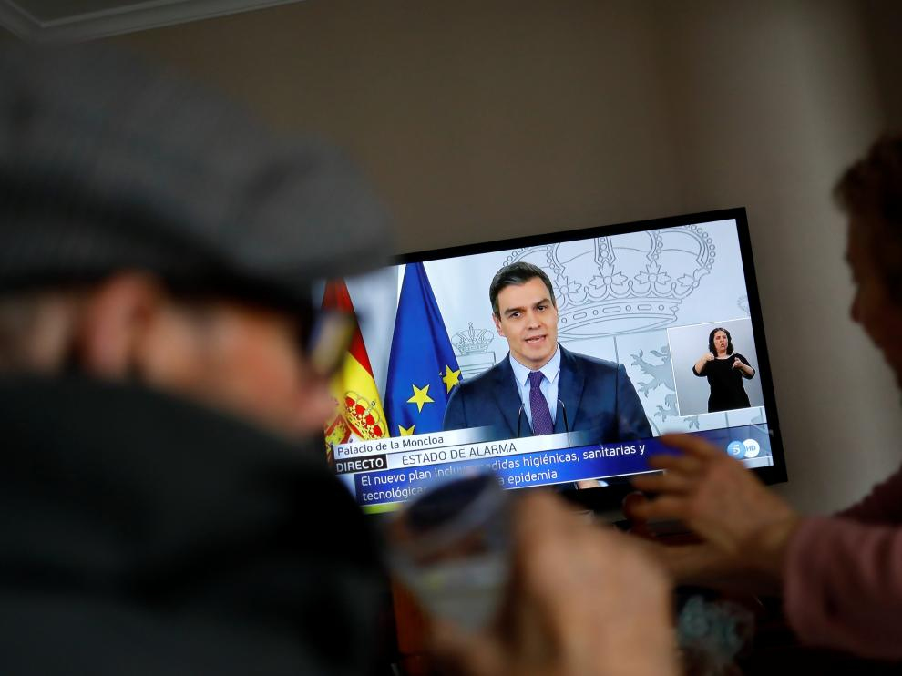 An elderly couple eats lunch at their home as they watch Spanish Prime Minister Pedro Sanchez on a television screen during a live news conference, due to the coronavirus disease (COVID-19) outbreak, in Ronda, southern Spain April 4, 2020. REUTERS/Jon Nazca [[[REUTERS VOCENTO]]] HEALTH-CORONAVIRUS/SPAIN