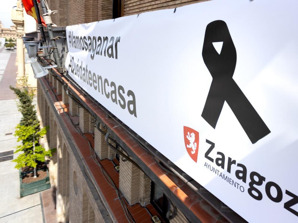pancarta colgada en el balcón municipal, a la que se ha añadido el crespón negro en recuerdo y homenaje de las víctimas del COVID-19 y sus familias.