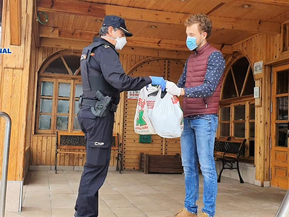 Un agente de la Policía Nacional entrega material al director de la residencia La Abubilla, en Yéqueda