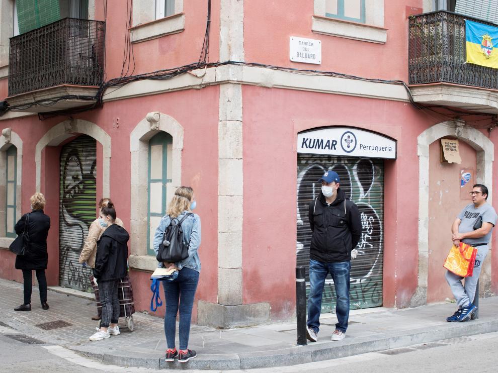 Vecinos en una fila para entrar en una tienda en el barrio de la Barceloneta.