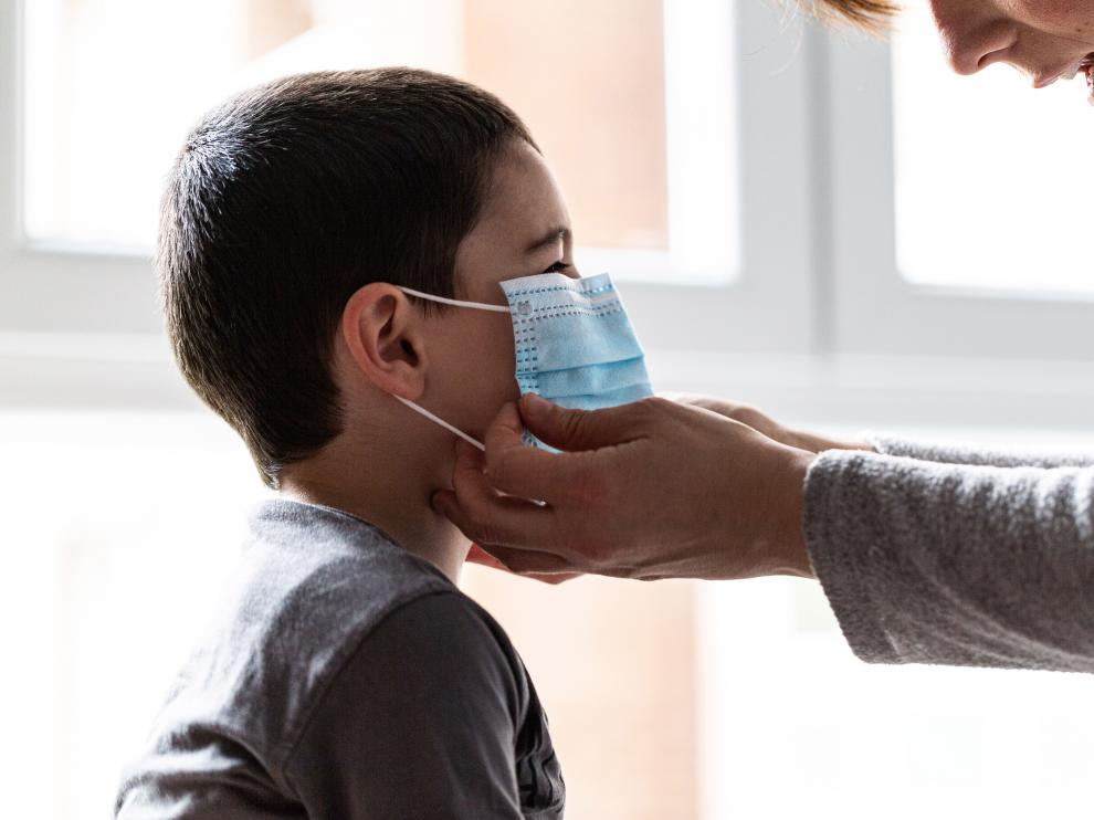 Una madre pone una mascarilla a su hijo.